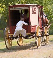 Boy hitching a ride on a horse drawn ice wagon. Goschenhoppen Folk Festival, The Antes Plantation, Perkiomenville PA